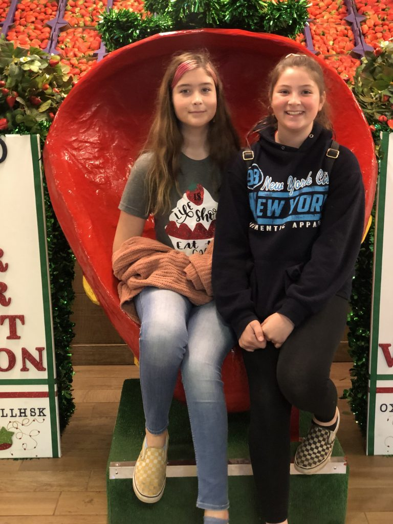two girls sitting on the strawberry throne at Strawberry Festival