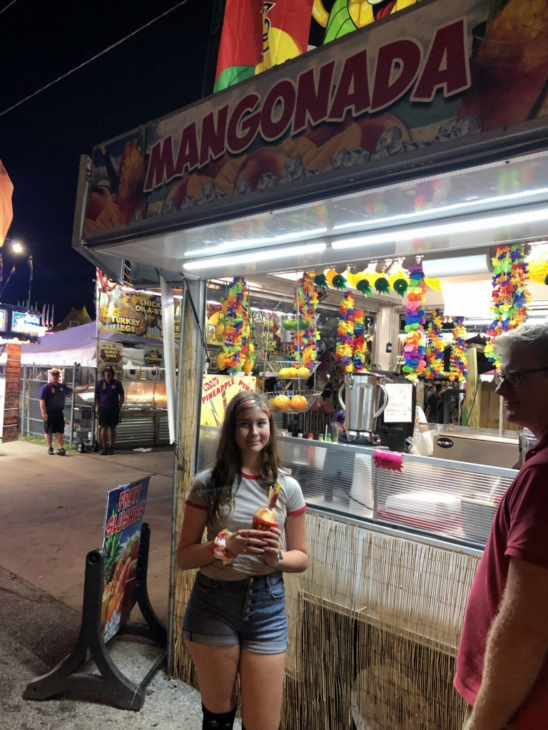 girl holding a slushie mangonada at the Florida Strawberry Festival.