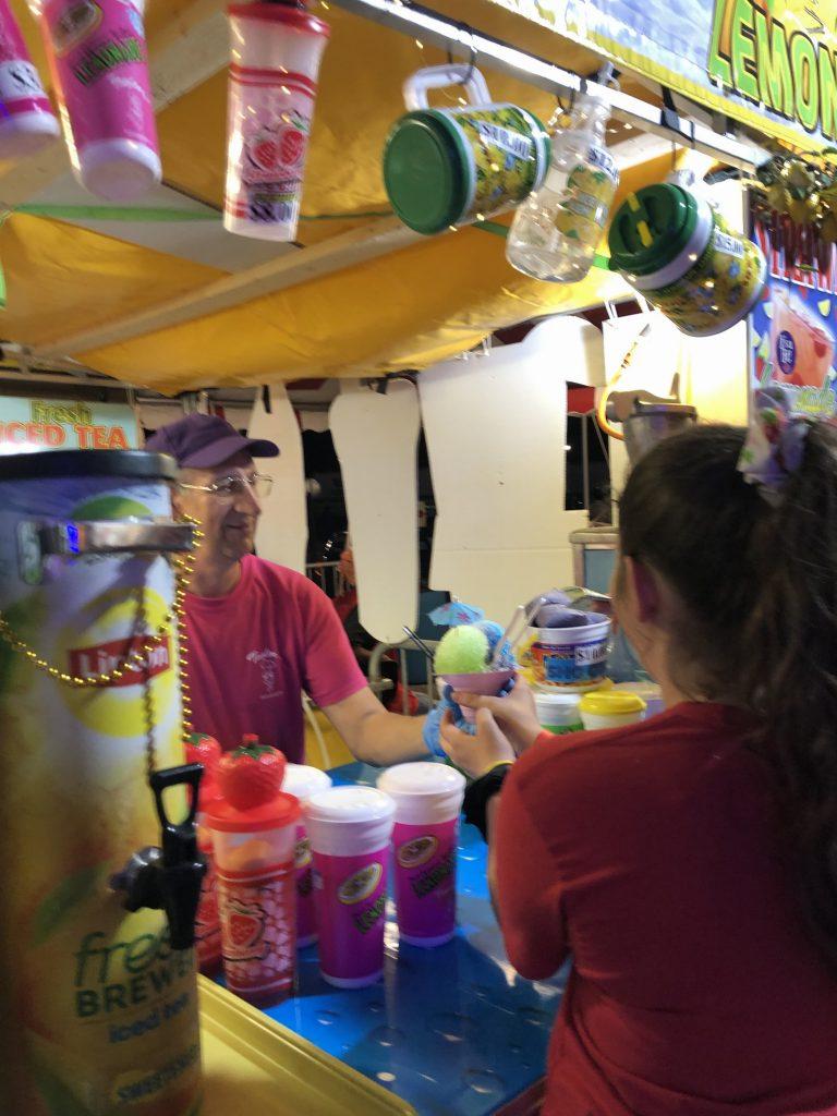 man handing out hawaiian ice cup to girl.